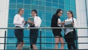 Τέσσερις ανοιχτόχρωμης επιδερμίδας επιχειρησιακές γυναίκες που στέκονται στο πεζούλι του κέντρου γραφείων και που συζητούν την επ φιλμ μικρού μήκους