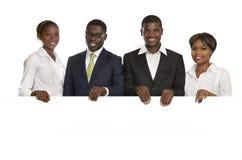 Τέσσερις αφρικανικοί επιχειρηματίες που κρατούν το άσπρο σημάδι, ελεύθερο διάστημα αντιγράφων Στοκ Εικόνες