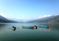 Τέσσερις βάρκες τουριστών multicolore της λίμνης Pheva, των βουνών και των σύννεφων Στοκ Εικόνες