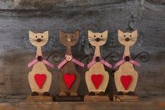 Τέσσερις βαλεντίνοι αγαπούν τις ξύλινες μορφές γατών με την κόκκινη διακόσμηση καρδιών Στοκ Εικόνα