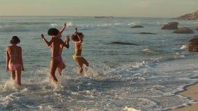 Τέσσερις γυναίκες στο παιχνίδι παραλιών στο νερό φιλμ μικρού μήκους