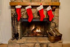 Τέσσερις γυναικείες κάλτσες Χριστουγέννων που κρεμιούνται από την εστία με προσοχή στοκ εικόνες