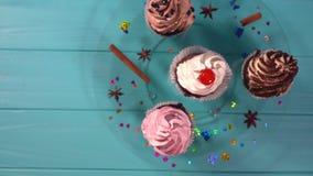 Τέσσερις διακοσμητικός που παγώνεται cupcakes με τα καρυκεύματα απόθεμα βίντεο