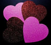 Τέσσερις διαφορετικές χρωματισμένες καρδιές glittery σε ένα μαύρο υπόβαθρο στοκ εικόνα με δικαίωμα ελεύθερης χρήσης