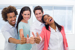 Τέσσερις εργαζόμενοι που δίνουν τους αντίχειρες επάνω και που χαμογελούν στη κάμερα Στοκ εικόνες με δικαίωμα ελεύθερης χρήσης