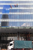 Τέσσερις εργαζόμενοι που πλένουν τα παράθυρα στο κτίριο γραφείων στοκ εικόνες με δικαίωμα ελεύθερης χρήσης