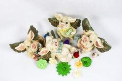 Τέσσερις ευτυχείς πετώντας χοίροι βαλεντίνων με τις καρδιές βρίσκονται γύρω σε έναν τομέα των λουλουδιών - τοπ άποψη Στοκ Εικόνες