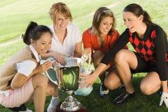 Τέσσερις θηλυκοί παίκτες γκολφ που σκύβουν γύρω από το τρόπαιο Στοκ φωτογραφία με δικαίωμα ελεύθερης χρήσης
