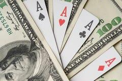 Τέσσερις κάρτες παιχνιδιού πόκερ άσσων μεταξύ του U S Δολάρια Στοκ φωτογραφία με δικαίωμα ελεύθερης χρήσης