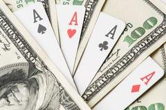 Τέσσερις κάρτες παιχνιδιού πόκερ άσσων μεταξύ του U S Δολάρια Στοκ Φωτογραφία