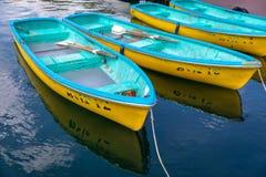 Τέσσερις κίτρινες και μπλε βάρκες σε ένα ακίνητο νερό λιμνών Στοκ εικόνες με δικαίωμα ελεύθερης χρήσης