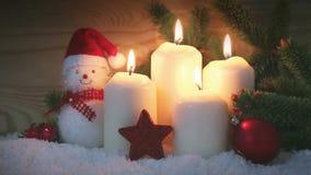 Τέσσερις καίγοντας κεριά και χιονάνθρωπος εμφάνισης με τις κόκκινες διακοσμήσεις Χριστουγέννων φιλμ μικρού μήκους