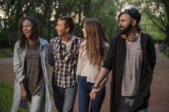 Τέσσερις και atractive νέοι που περπατούν μαζί στο πάρκο Άνθρωποι που φορούν τα περιστασιακά ενδύματα Στοκ Φωτογραφία