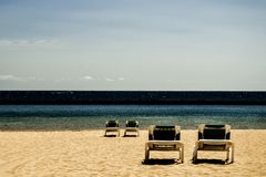 Τέσσερις καρέκλες ξαπλώματος σε μια παραλία (αντίθεση) στοκ εικόνες