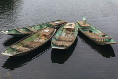 Τέσσερις κενές βάρκες κωπηλασίας σταματούν πέρα από τον ποταμό σε Trang ένα Grottoes σε Ninh Binh, Βιετνάμ Στοκ Φωτογραφία