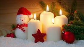 Τέσσερις λευκοί κάψιμο και χιονάνθρωπος κεριών εμφάνισης απόθεμα βίντεο