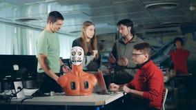 Τέσσερις μηχανικοί που εργάζονται μαζί με ένα humanoid, cyborg, ρομπότ απόθεμα βίντεο