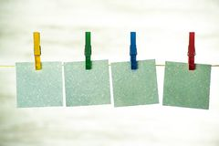 Τέσσερις μπλε κάρτες που κρεμούν σε μια σειρά, που στερεώνεται με τις ζωηρόχρωμες πόρπες στοκ εικόνες με δικαίωμα ελεύθερης χρήσης
