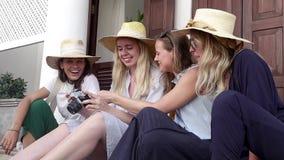 Τέσσερις νέες μοντέρνες γυναίκες στα καπέλα αχύρου κάθονται στην οδό απόθεμα βίντεο