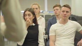 Τέσσερις νέοι αρσενικοί και θηλυκοί διευθυντές στην επίσημη ένδυση που ακούνε τη συνεδρίαση ομιλητών στο μικρό δωμάτιο γραφείων απόθεμα βίντεο