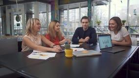 Τέσσερις νέοι ενήλικοι επιχειρηματίες συζητούν τις νέες στρατηγικές στο ξεκίνημα χρησιμοποιώντας τα lap-top σύγχρονα στη μεγάλη π απόθεμα βίντεο