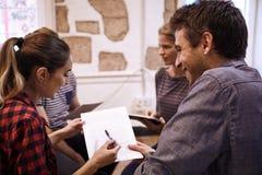 Τέσσερις νέοι επαγγελματίες στην ενδιαφέρουσα συζήτηση Στοκ Φωτογραφίες