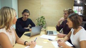Τέσσερις νέοι επιχειρηματίες συζητούν τις νέες στρατηγικές στο ξεκίνημα χρησιμοποιώντας τα lap-top στην αίθουσα συνεδριάσεων των  απόθεμα βίντεο