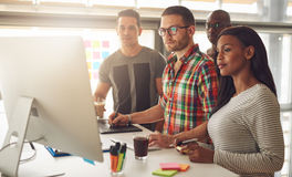Τέσσερις νέοι εργαζόμενοι που στέκονται γύρω από τον υπολογιστή στοκ εικόνες