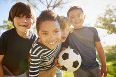 Τέσσερις νέοι μαθητές που κλίνουν μέσα στο ποδόσφαιρο εκμετάλλευσης καμερών στοκ φωτογραφίες με δικαίωμα ελεύθερης χρήσης