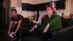 Τέσσερις νέοι που κάθονται στον καναπέ και που έχουν τη διασκέδαση που προσέχει τον αγώνα ποδοσφαίρου Το συγκινημένο άτομο που στ απόθεμα βίντεο