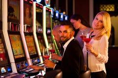 Τέσσερις νέοι που παίζουν τα μηχανήματα τυχερών παιχνιδιών με κέρματα στη χαρτοπαικτική λέσχη Στοκ Φωτογραφία