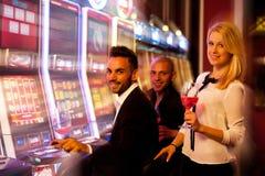 Τέσσερις νέοι που παίζουν τα μηχανήματα τυχερών παιχνιδιών με κέρματα στη χαρτοπαικτική λέσχη Στοκ Εικόνες