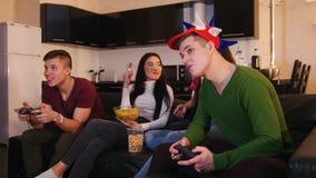 Τέσσερις νέοι που περνούν καλά μαζί, παίζοντας παιχνίδι νεαρών άνδρων δύο η ομιλία φίλων τους απόθεμα βίντεο