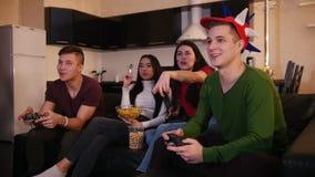 Τέσσερις νέοι που περνούν καλά μαζί, παίζοντας παιχνίδι νεαρών άνδρων δύο ενώ οι φίλες τους που μιλούν πέρα από το παιχνίδι φιλμ μικρού μήκους
