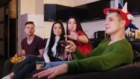 Τέσσερις νέοι που προσέχουν τη TV Η νέα γυναίκα προσπαθεί να πάρει τη TV μακρινή από τον τύπο απόθεμα βίντεο
