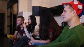 Τέσσερις νέοι που προσέχουν τον αγώνα ποδοσφαίρου, που τρώνε το άχρηστο φαγητό και που συζητούν το παιχνίδι απόθεμα βίντεο