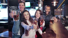 Τέσσερις παλιοί φίλοι στο φραγμό με ένα ποτήρι της μπύρας απόθεμα βίντεο