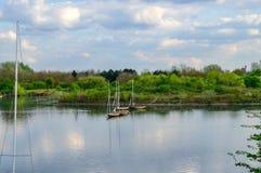 Τέσσερις πλέοντας βάρκες που δένονται στην ήρεμη λίμνη Στοκ Εικόνες