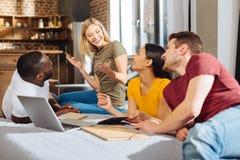 Τέσσερις σφριγηλοί νέοι σπουδαστές που προσκαλούν τη συσκευή στοκ εικόνες