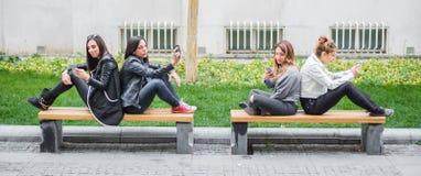 Τέσσερις φίλοι κοριτσιών που χρησιμοποιούν τα κινητά τηλέφωνα στον πάγκο πάρκων Στοκ φωτογραφίες με δικαίωμα ελεύθερης χρήσης