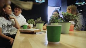 Τέσσερις φίλοι κουβεντιάζουν και γελούν συνεδρίαση σε έναν καφέ, και κάποιος εμφανίστηκε ήσυχα και έβαλε έναν λογαριασμό χρημάτων απόθεμα βίντεο