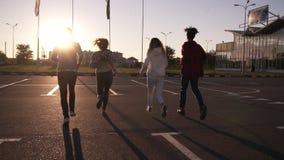 Τέσσερις φίλοι τρέχουν από την κενή ζώνη χώρων στάθμευσης υπαίθρια - η ευτυχία διασκέδασης, οι νεαροί άνδρες και οι γυναίκες τρέχ απόθεμα βίντεο