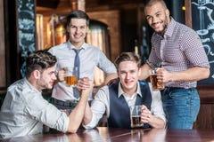 Τέσσερις φίλοι που έχουν τη διασκέδαση και που πίνουν την μπύρα και ξοδεύουν το χρόνο togethe Στοκ φωτογραφία με δικαίωμα ελεύθερης χρήσης