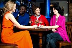 Τέσσερις φίλοι που απολαμβάνουν το γεύμα σε ένα εστιατόριο Στοκ Εικόνες