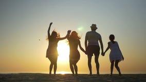 Τέσσερις φίλοι που πηδούν στην παραλία στο ηλιοβασίλεμα σε σε αργή κίνηση φιλμ μικρού μήκους