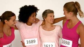 Τέσσερις χαμογελώντας θηλυκοί αθλητές με τα όπλα γύρω απόθεμα βίντεο