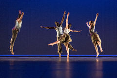 Τέσσερις χορευτές θέτουν στο σκοτεινό κλίμα στη σκηνή Στοκ Εικόνες