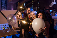 Τέσσερις όμορφες νέες καυκάσιες γυναίκες που κρατούν τα μπαλόνια που έχουν τη νύχτα έξω μαζί στον καθιερώνοντα τη μόδα φραγμό στοκ φωτογραφίες