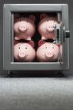 Τέσσερις piggy τράπεζες στο χρηματοκιβώτιο Στοκ φωτογραφία με δικαίωμα ελεύθερης χρήσης
