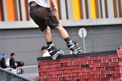 Τέχνασμα άλματος Rollerblade σε ένα υπόβαθρο πόλεων Στοκ εικόνα με δικαίωμα ελεύθερης χρήσης